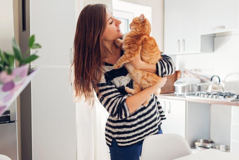 Junge Frau, die zu Hause mit Katze in der Küche spielt Mädchen, das Ingwerkatze hält und umarmt stockbild