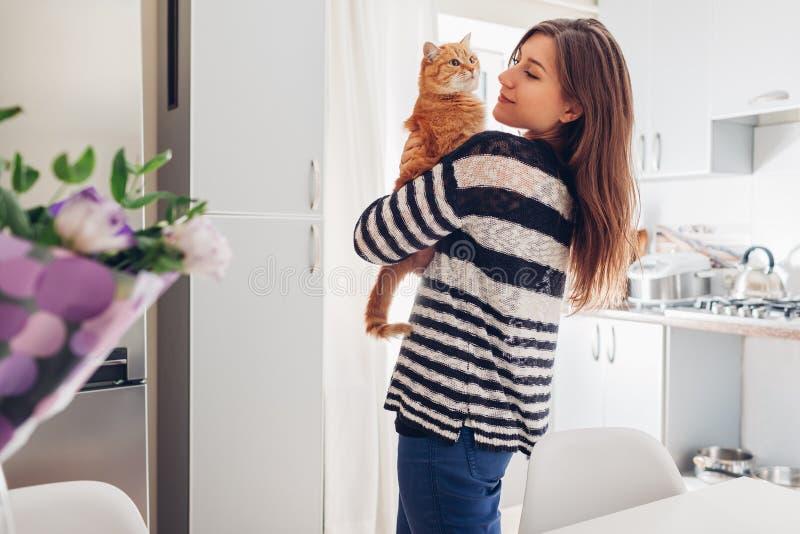 Junge Frau, die zu Hause mit Katze in der Küche spielt Mädchen, das rote Katze hält und züchtet lizenzfreie stockfotos