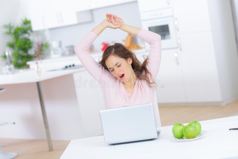 Junge Frau, die zu Hause mit Laptop gähnt lizenzfreies stockfoto