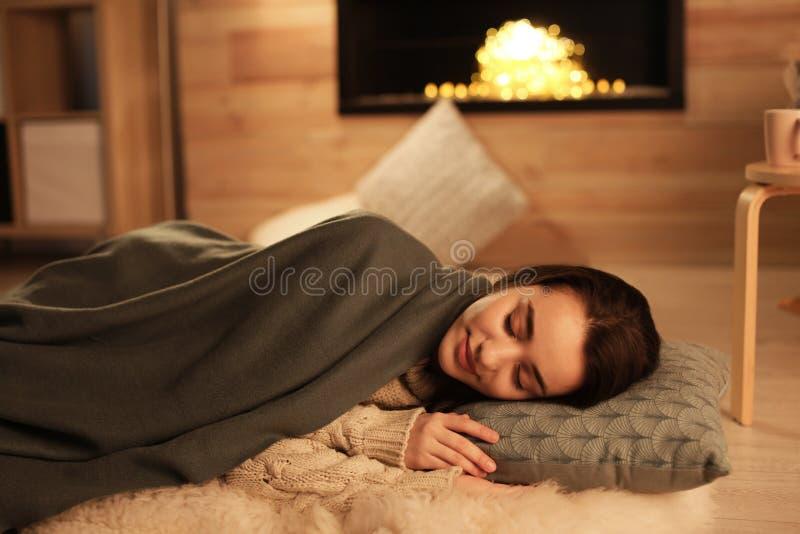 Junge Frau, die zu Hause nahe dekorativem Kamin schläft stockfoto