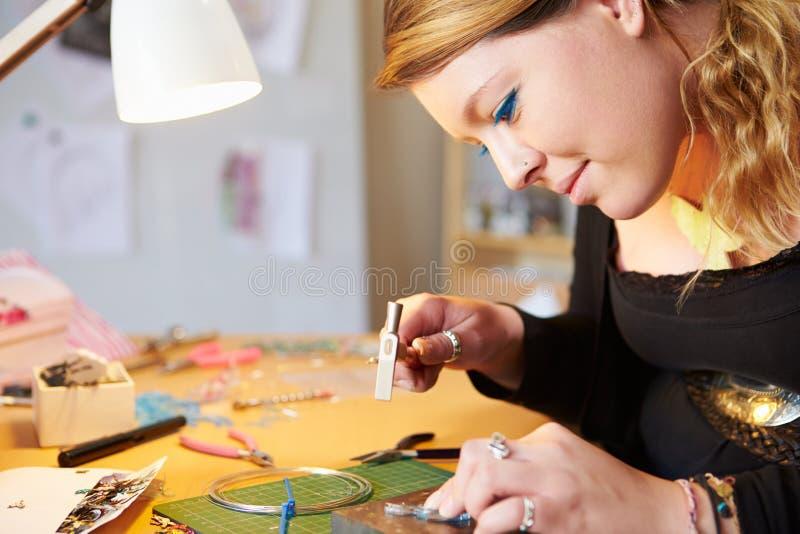 Junge Frau, die zu Hause Schmuck macht stockbilder