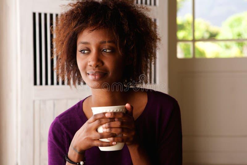 Junge Frau, die zu Hause Tasse Kaffee genießt lizenzfreie stockfotos