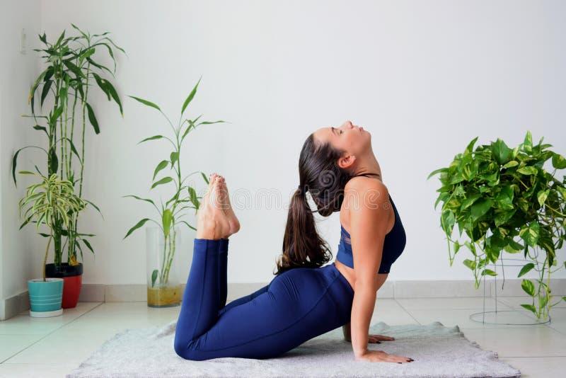 Junge Frau, die zu Hause Yoga tut lizenzfreie stockfotografie