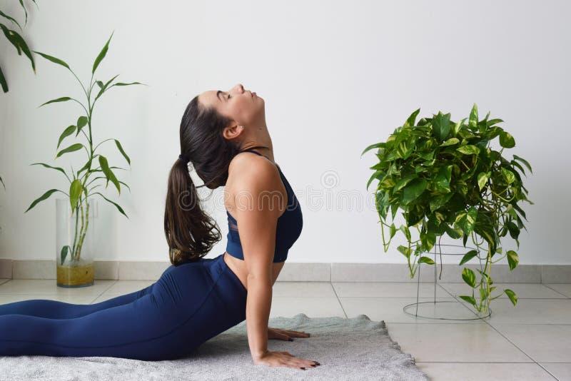 Junge Frau, die zu Hause Yoga tut lizenzfreies stockfoto