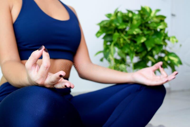 Junge Frau, die zu Hause Yoga tut lizenzfreie stockfotos