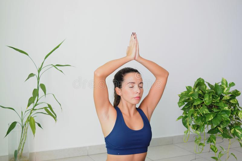 Junge Frau, die zu Hause Yoga tut stockbild