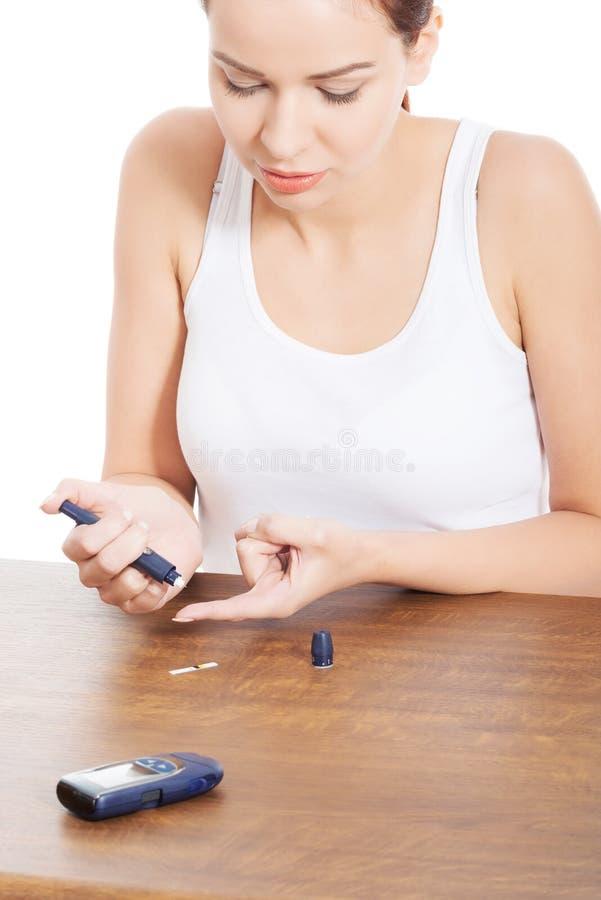 Junge Frau, die Zuckergehalttest durchführt. stockfoto