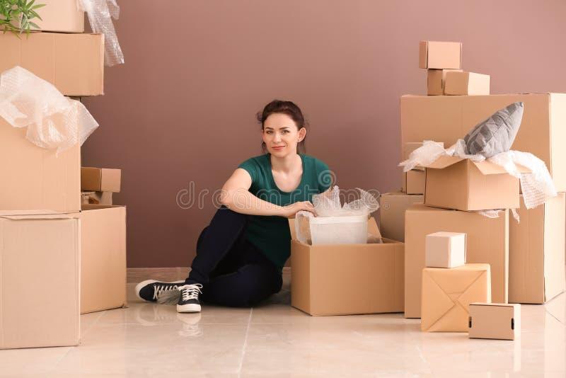 Junge Frau, die zuhause Kästen auspackt Bewegen in neues Haus lizenzfreie stockbilder