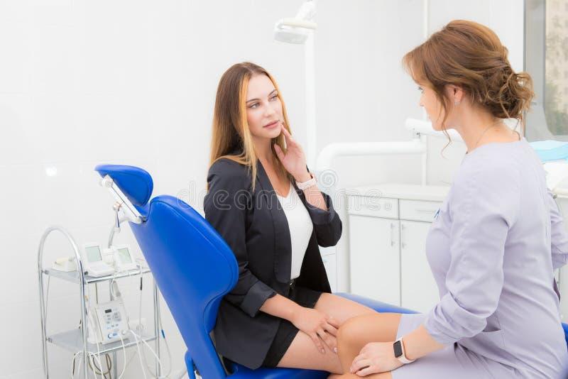 Junge Frau, die zum Zahnarzt über Zahnschmerzen sich beschwert stockbilder