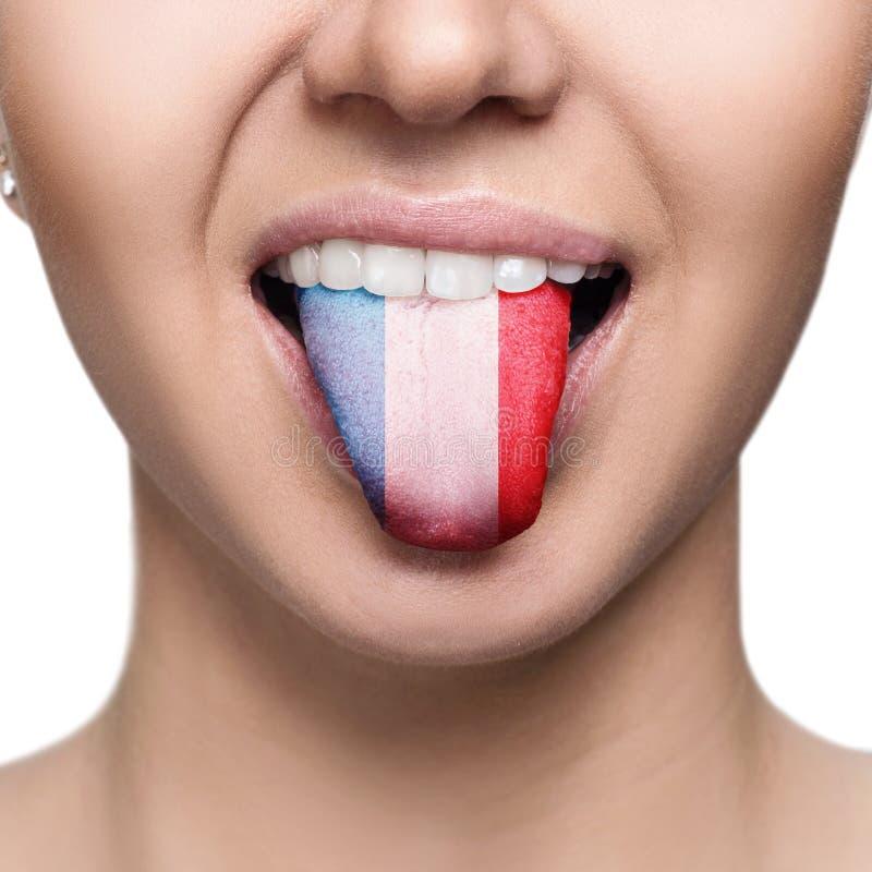 Junge Frau, die Zunge mit Frankreich-Flagge zeigt stockbilder