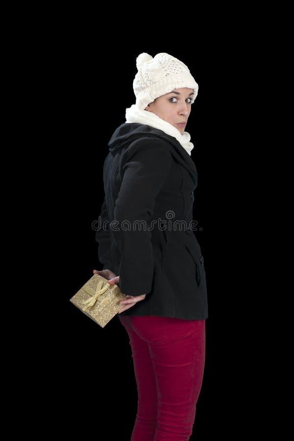 Junge Frau, die zurück ein Geschenk hinter ihr versteckt stockfotografie