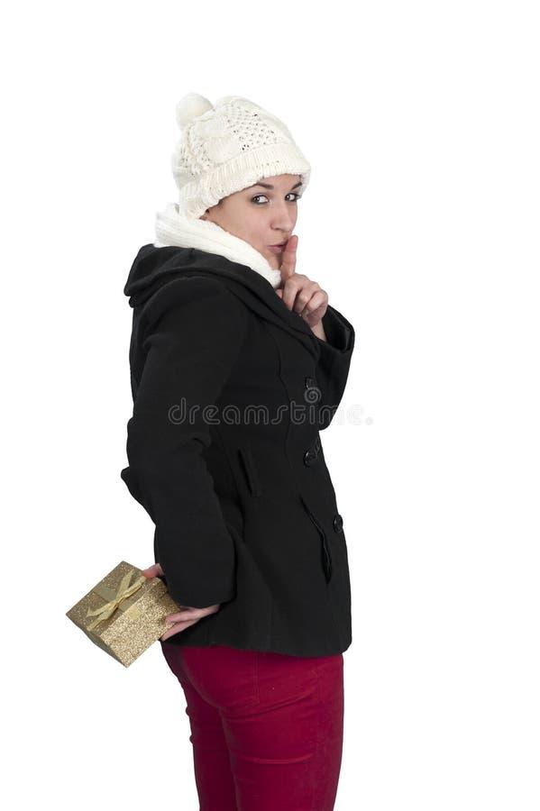 Junge Frau, die zurück ein Geschenk hinter ihr versteckt lizenzfreie stockfotografie