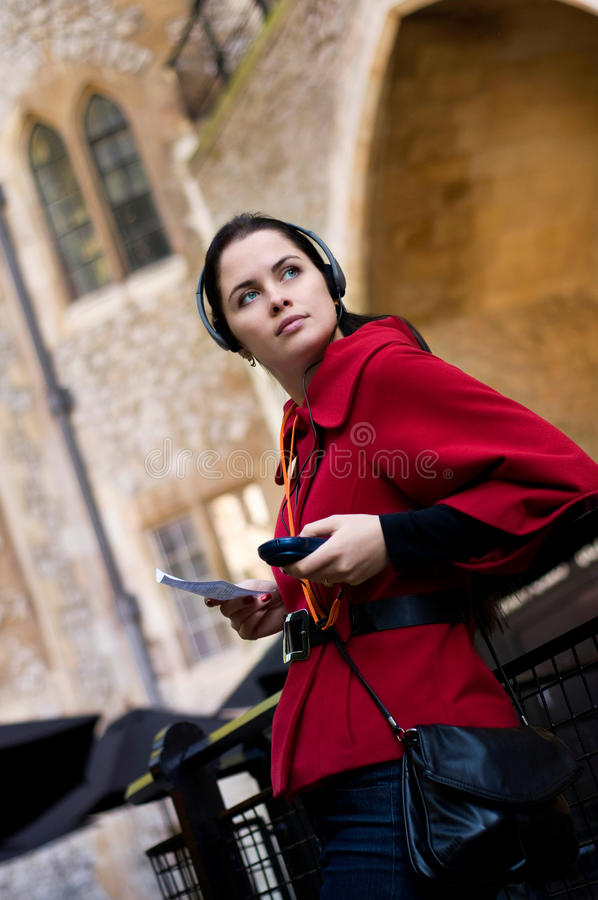 Junge Frau, die zur Audioanleitung hört lizenzfreie stockfotografie