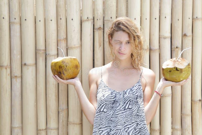 Junge Frau, die zwei frische Kokosnüsse hält stockfoto