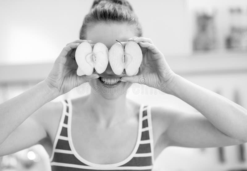 Junge Frau, die zwei Scheiben Apfel vor Augen hält stockbilder