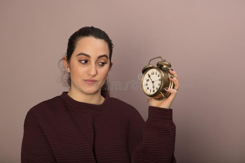Junge Frau, die zweifelhaft einem Wecker betrachtet lizenzfreies stockfoto