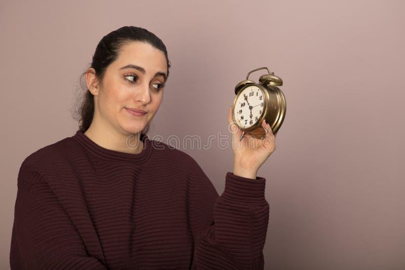 Junge Frau, die zweifelhaft einem Wecker betrachtet stockbilder