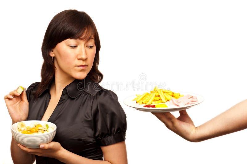 Junge Frau, die zwischen gesundem Salat und Frei wählt lizenzfreie stockfotos