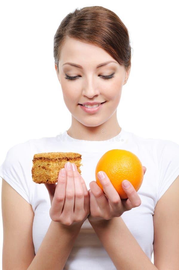 Junge Frau, die zwischen Kuchen und Orange wählt lizenzfreie stockfotografie