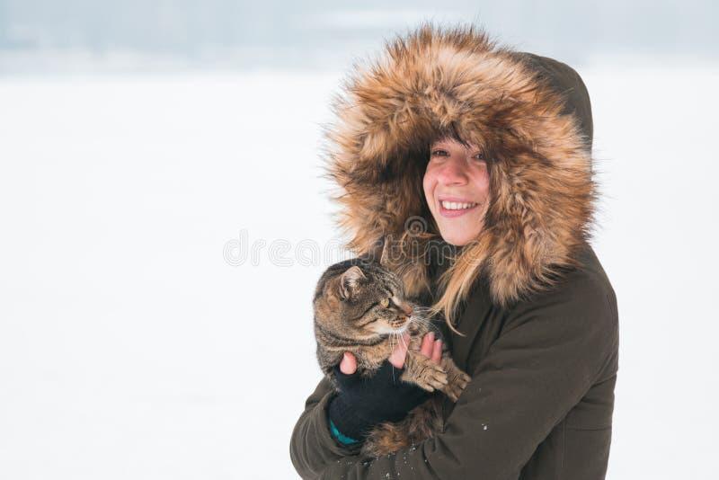 Junge Frau draußen im Winter eine Katze halten lizenzfreie stockfotografie