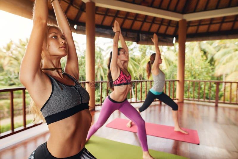 Junge Frau drei, die Yoga an der Klasse tut stockfotografie