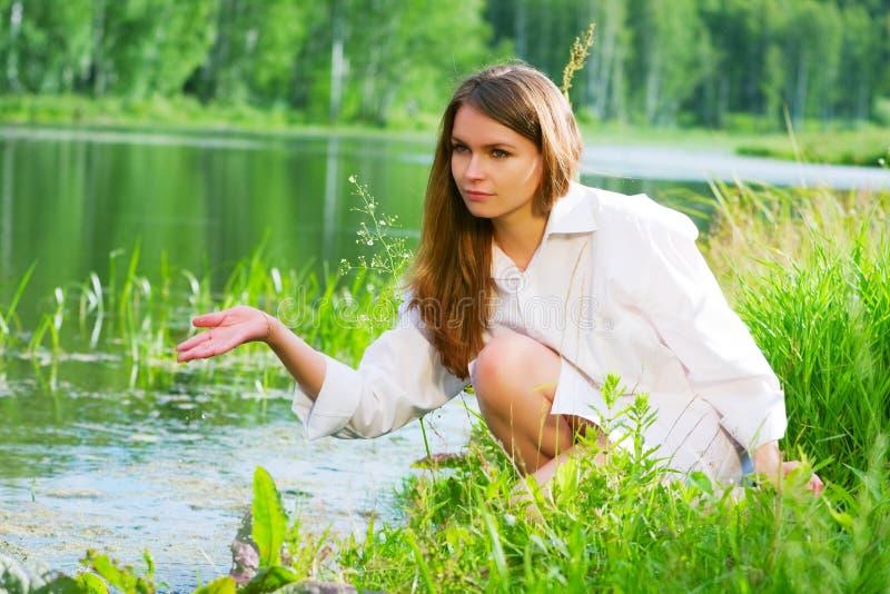 Junge Frau durch den See stockbild