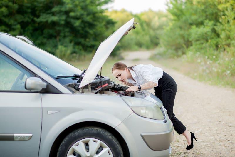 Junge Frau durch den Straßenrand, nachdem ihr Auto aufgegliedert sie hat, öffnete die Haube, um den Schaden zu sehen lizenzfreie stockbilder