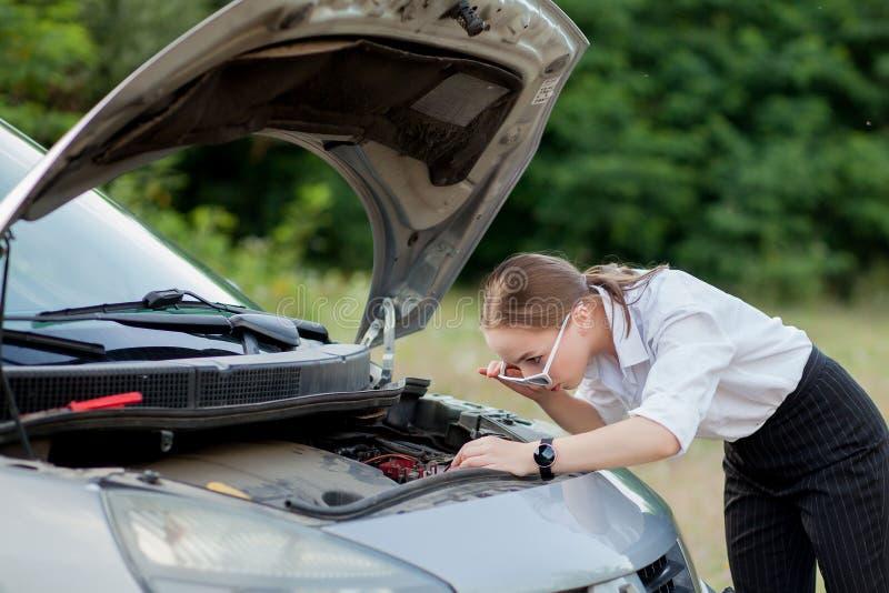 Junge Frau durch den Straßenrand, nachdem ihr Auto aufgegliedert sie hat, öffnete die Haube, um den Schaden zu sehen stockfotos