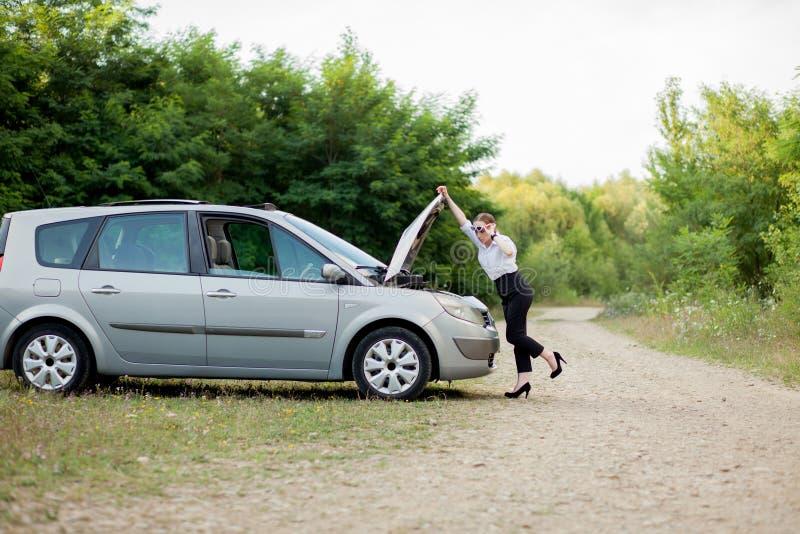 Junge Frau durch den Straßenrand, nachdem ihr Auto aufgegliedert sie hat, öffnete die Haube, um den Schaden zu sehen stockbild