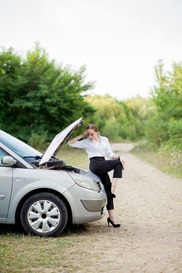 Junge Frau durch den Straßenrand, nachdem ihr Auto aufgegliedert sie hat, öffnete die Haube, um den Schaden zu sehen lizenzfreies stockbild