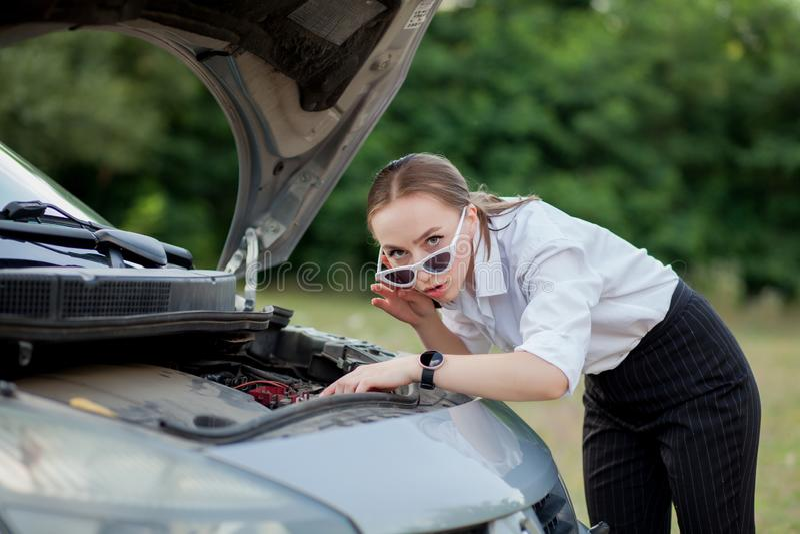 Junge Frau durch den Straßenrand, nachdem ihr Auto aufgegliedert sie hat, öffnete die Haube, um den Schaden zu sehen stockfoto