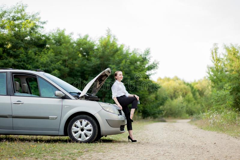 Junge Frau durch den Straßenrand, nachdem ihr Auto aufgegliedert sie hat, öffnete die Haube, um den Schaden zu sehen stockbilder