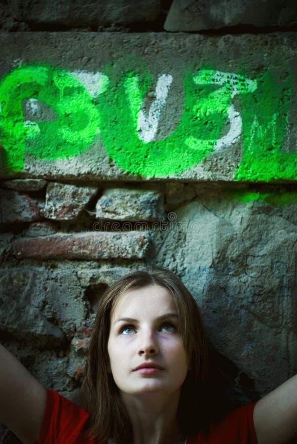 Junge Frau durch Steinwand lizenzfreie stockfotografie