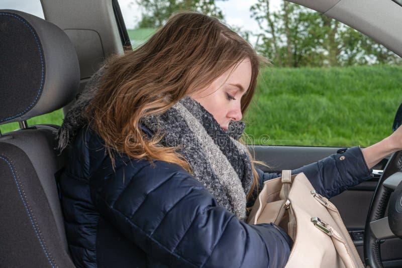 Junge Frau durchstöbert während Autofahren in ihrer Tasche und wird abgelenkt lizenzfreies stockbild