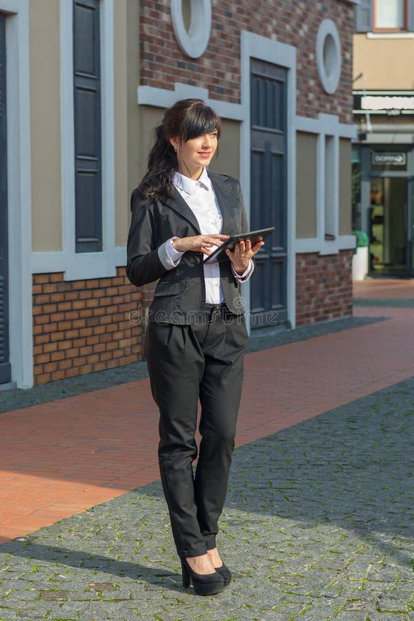 Junge Frau in einem Anzug mit einer Tablette steht auf einer Straße lizenzfreies stockfoto