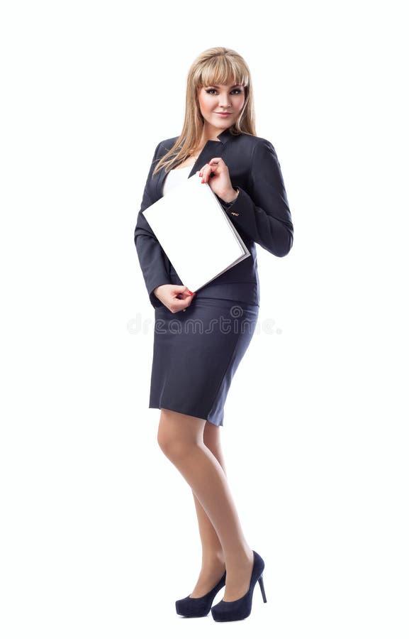 Junge Frau in einem Anzug zeigt leeres weißes Blatt, stockfotografie