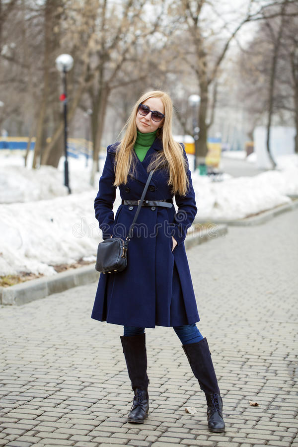 Junge Frau in einem blauen Mantel lizenzfreies stockbild