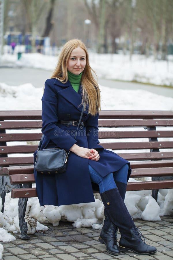 Junge Frau in einem blauen Mantel, der auf einer Bank im Winterpark sitzt lizenzfreie stockfotografie