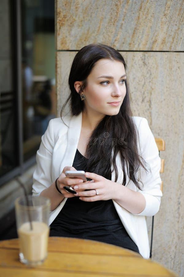 Junge Frau in einem Café im Freien lizenzfreie stockfotos