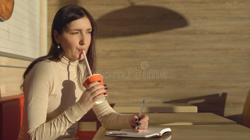 Junge Frau in einem Café macht Anmerkungen in einem Notizbuch und trinkt Saft lizenzfreies stockbild