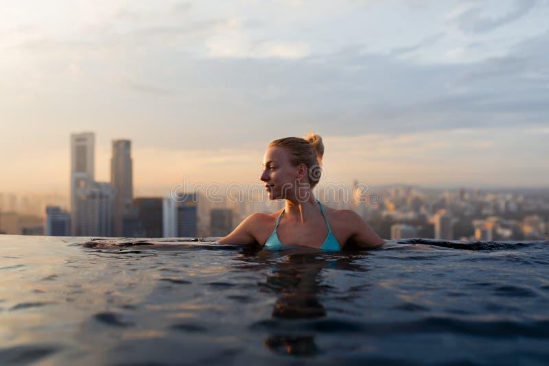 Junge Frau in einem Dachspitzen-Swimmingpool mit schöner Stadtansicht lizenzfreie stockfotografie