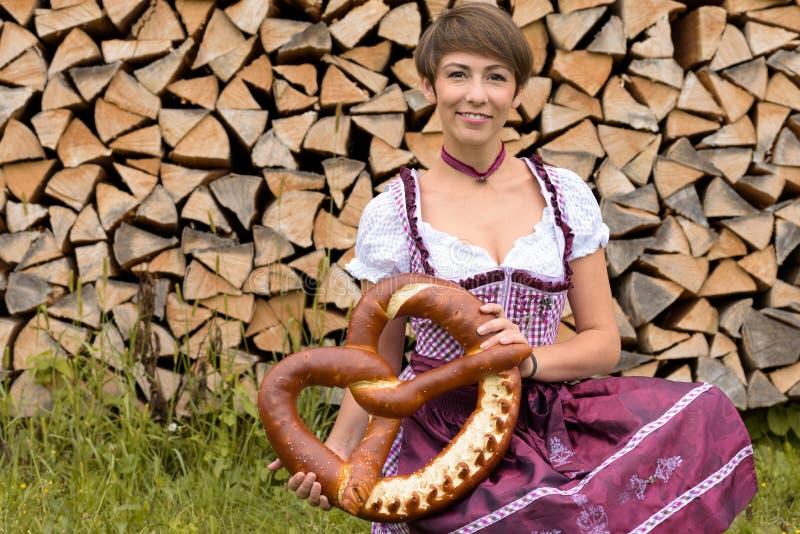 Junge Frau in einem Dirndl, der eine große Brezel hält lizenzfreies stockfoto