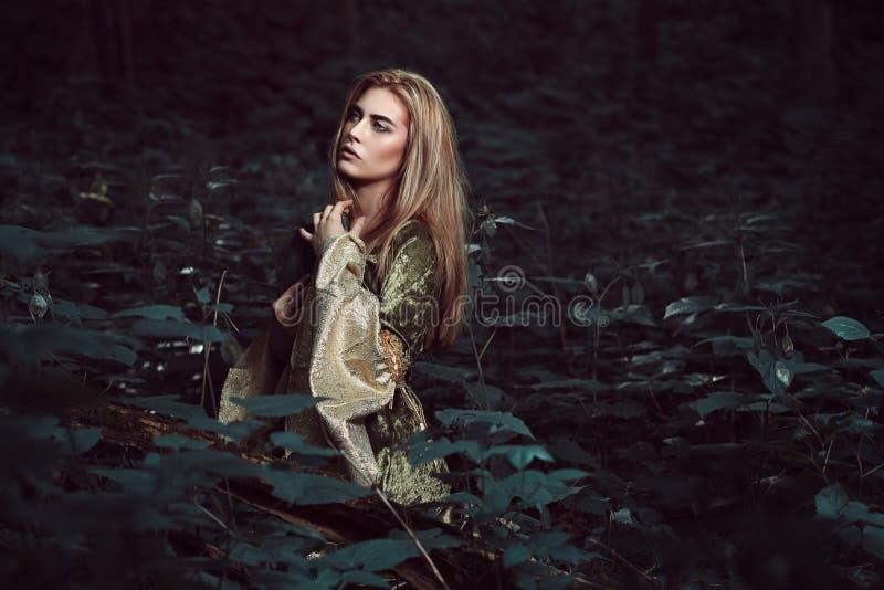 Junge Frau in einem dunklen feenhaften Wald lizenzfreie stockbilder