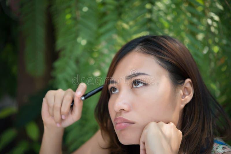 Junge Frau in einem durchdachten Garten der Haltung zu Hause neues Pro denkend stockbild