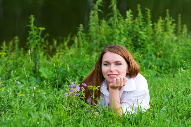 Junge Frau in einem Gras stockfotos