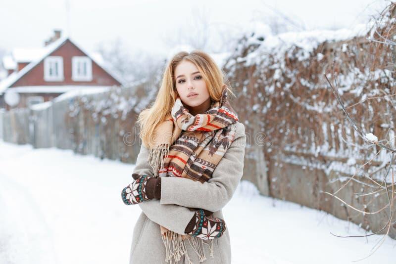 Junge Frau in einem grauen Mantel der Weinlese in einem woolen stilvollen Schal in den warmen woolen Handschuhständen am Winterna stockfoto