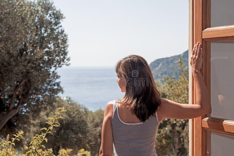 Junge Frau an einem großen offenen Fenster Abstraktes Foto des Sommers lizenzfreie stockfotografie