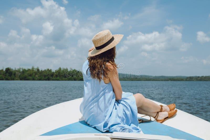 Junge Frau in einem Hut sitzt auf der Front des Segelboots und bewundert die Ansicht lizenzfreies stockbild