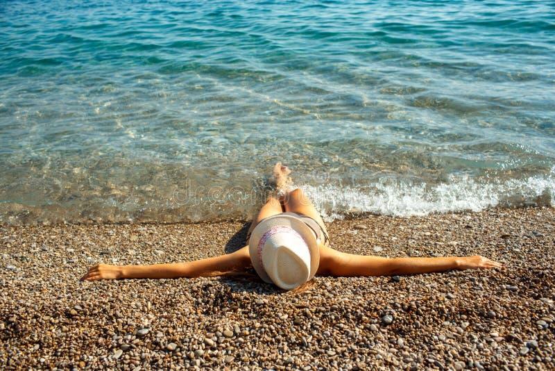 Junge Frau in einem Hut und in einem Bikini, die auf dem Strand im heißen Sommer liegen stockfoto