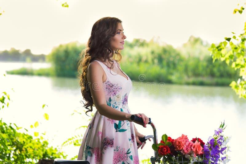 Junge Frau in einem Kleid und in einem Hut auf einem Fahrrad auf der Natur im Th lizenzfreie stockfotografie